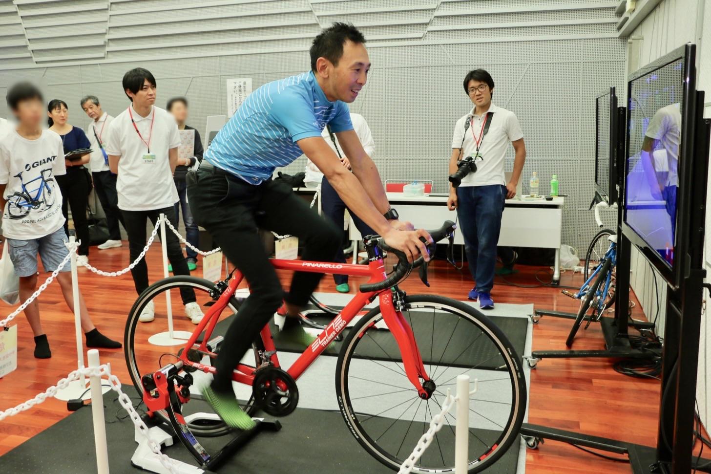 固定自転車による市内コース(尾根幹線)とツール・ド・フランスのコースのバーチャル走行シュミレーション体験が行われ、田代さんによるデモ走行も