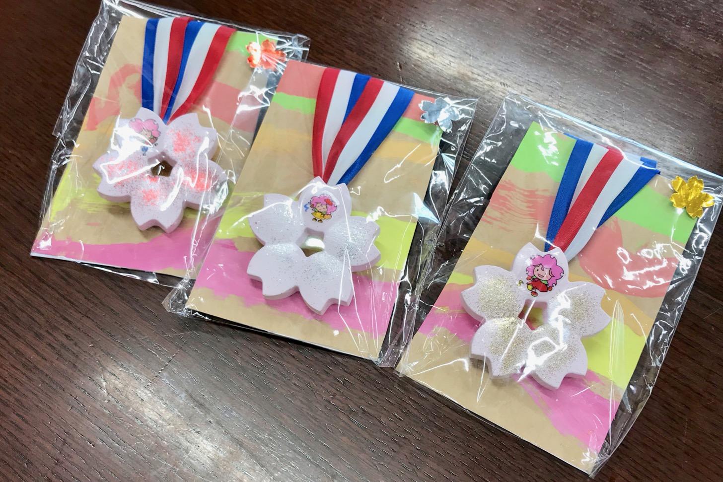 1位から3位までの東京都立多摩桜の丘学園(特別支援学校)の子どもたちが作ったメダルが授与